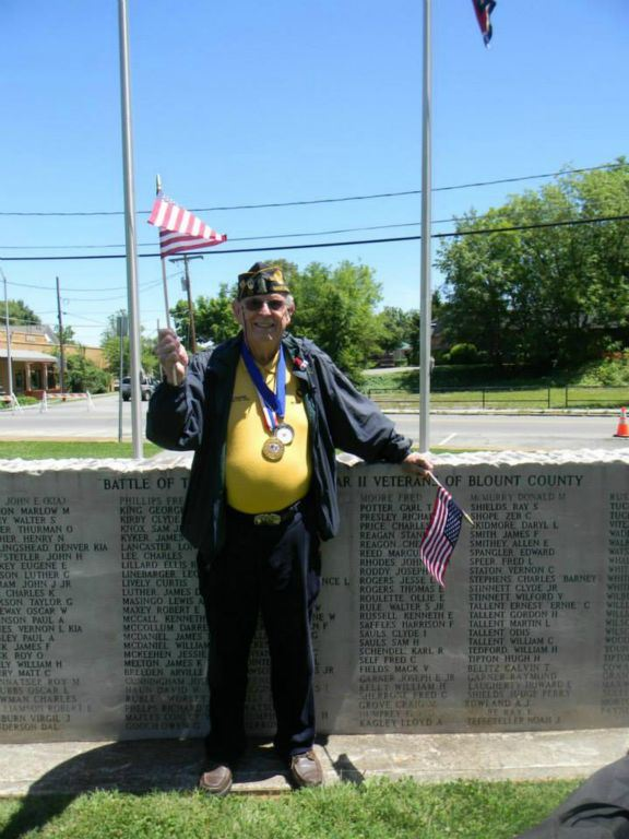 Image of veteran leaning on war memorial waving miniature American flag